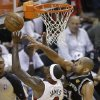 Photo - San Antonio Spurs power forward Tim Duncan (21) blocks a drive to the basket by Miami Heat small forward LeBron James (6)during the first half of Game 1 of basketball's NBA Finals, Thursday, June 6, 2013 in Miami. (AP Photo/Wilfredo Lee)