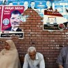 Egyptians sit beneath campaign posters supporting the Muslim Brotherhood\'s presidential candidate Mohammed Morsi outside a polling center as they wait to cast their votes in Alexandria, Egypt, Wednesday, May 23, 2012. More than 15 months after autocratic leader Hosni Mubarak\'s ouster, Egyptians streamed to polling stations Wednesday to freely choose a president for the first time in generations. Waiting hours in line, some debated to the last minute over their vote in a historic election pitting old regime figures against ascending Islamists.(AP Photo/Khalil Hamra) ORG XMIT: KH120