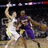 Photo - Los Angeles Lakers' Kobe Bryant (24) dribbles next to Golden State Warriors' Klay Thompson (11) during the first half of an NBA basketball game in Oakland, Calif., Saturday, Dec. 22, 2012. (AP Photo/Marcio Jose Sanchez)