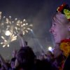 Photo - CORRECTS DATE -Fireworks illuminate the sky as German fans celebrate their team after  Germany  won  against Argentina  by 1-0 at the soccer World Cup final in Rio de Janeiro, Brazil,  at a public viewing area called 'Fan Mile'  in Berlin,  early Monday July 14, 2014. (AP Photo/dpa,.Britta Pedersen)