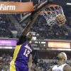 Photo - Los Angeles Lakers center Dwight Howard, left, dunks over Sacramento Kings center DeMarcus Cousins during the first quarter of an NBA basketball game in Sacramento, Calif., Saturday, March 30, 2013. (AP Photo/Rich Pedroncelli)