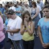 Alyssa Hernandez, center right, and Isabella Dominguez pray during a vigil near CiCi\'s Pizza Monday, June 9, 2014 in Las Vegas. The vigil was held to honor two Las Vegas Metropolitan Police officers and a bystander who were killed on Sunday. (AP Photo/John Locher)