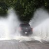 A pickup truck creates a huge splash as it drives through water on the road around Shield\'s Lake near the Maymont Nature Center in Richmond, Va., Thursday, June 13, 2013 after a strong line of storms moved through the area. (AP Photo/Richmond Times-Dispatch, Bob Brown).
