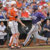 Photo - TCU's Garrett Crain, right, crosses home plate with Virginia catcher Nate Irving (18) looking on, left, on a single by TCUs Dylan Fitzgerald,  in the second inning of an NCAA baseball College World Series game in Omaha, Neb., Tuesday, June 17, 2014. (AP Photo/Ted Kirk)