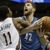 Photo - Milwaukee Bucks' Brandon Knight (11) fouls Minnesota Timberwolves' Kevin Love (42) during the first half of an NBA basketball game, Saturday, Dec. 28, 2013, in Milwaukee. (AP Photo/Jeffrey Phelps)