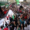 In this citizen journalism image provided by Aleppo Media Center AMC which has been authenticated based on its contents and other AP reporting, anti-Syrian regime protesters raise up their hands as they wave Syrian revolutionary flags during a protest to mark the second anniversary of the their uprising, in Aleppo, Syria, Friday March 15, 2013. The chief of Syria\'s main, western-backed rebel group marked the second anniversary of the start of the uprising against President Bashar Assad on Friday by pledging to fight until the