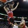 Photo - Washington Wizards power forward Jan Vesely (24) slam dunks over center Marcin Gortat, right, and New Orleans Pelicans shooting guard Eric Gordon (10) in the first half of an NBA basketball game in New Orleans, Wednesday, Jan. 8, 2014. (AP Photo/Gerald Herbert)