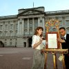 The Queen\'s Press Secretary Ailsa Anderson, with Badar Azim, a footman, places an official document to announce the birth of a baby boy, at 4.24pm to the Duke and Duchess of Cambridge at St Mary\'s Hospital, in the forecourt of Buckingham Palace in London Monday July 22, 2013. The child is now third in line to the British throne. (AP Photo/John Stillwell, Pool)