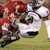 Photo - OU's Demontre Hurst, bottom left, and Tom Wort tackle Utah State's Xavier Martin during the second half of the college football game between the University of Oklahoma Sooners (OU) and Utah State University Aggies (USU) at the Gaylord Family-Oklahoma Memorial Stadium on Saturday, Sept. 4, 2010, in Norman, Okla.   Photo by Bryan Terry, The Oklahoman