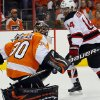 Photo -   Philadelphia Flyers' Ilya Bryzgalov, left, deflects a shot as New Jersey Devils' Adam Henrique tries for the rebounding puck during the first period in Game 2 of an NHL hockey Stanley Cup second-round playoff series, Tuesday, May 1, 2012, in Philadelphia. (AP Photo/Tom Mihalek)