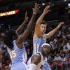 Miami Heat forward LeBron James, center, looks for an opening past Denver Nuggets forwards Kenneth Faried (35) and Danilo Gallinari, rear, during the first half of an NBA basketball game, Saturday, Nov. 3, 2012 in Miami. (AP Photo/Wilfredo Lee)