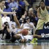 Photo - Duke's Oderah Chidom, center, passes the ball as Georgia Tech's Katarina Vuckovic, left, and Roddreka Rogers, right, defend during the first half of an NCAA college basketball game at the Atlantic Coast Conference tournament in Greensboro, N.C., Friday, March 7, 2014. (AP Photo/Chuck Burton)
