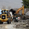 Workers using heavy equipment work to clear debris Tuesday, March 25, 2014, from Washington Highway 530 on the western edge of the massive mudslide that struck near Arlington, Wash., Saturday, killing at least 14 people and leaving dozens missing. (AP Photo/Ted S. Warren, Pool)