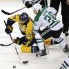 Photo - Nashville Predators forward Paul Gaustad (28) passes the puck away from Dallas Stars center Cody Eakin (20) in the second period of an NHL hockey game Monday, Jan. 20, 2014, in Nashville, Tenn. (AP Photo/Mark Humphrey)
