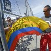 Photo - Juan Pablo Montoya, of Colombia, signs a flag for a fan before a racing practice session for the NASCAR Sprint Cup auto race at Daytona International Speedway  Thursday, July 4, 2013, in Daytona Beach, Fla. (AP Photo/Phelan M. Ebenhack)