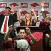Arkansas football coach Bret Bielema, top left, his wife, Jen, center, and athletic director Jeff Long, right,
