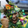 Photo - A Brazil soccer fan covered in flowers and his nation's flag cheers inside the FIFA Fan fest area before the start of the World Cup openes between Brazil and Croatia on Copacabana beach, Rio de Janeiro, Brazil, Thursday, June 12, 2014. After taking the early lead in the opening match of the international soccer tournament, Croatia fell 3-1 to the five-time champion Brazil. (AP Photo/Silvia Izquierdo)