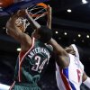 Photo - Milwaukee Bucks guard Giannis Antetokounmpo (34) gets past Detroit Pistons forward Josh Smith, right, for a dunk during the first half of an NBA basketball game Monday, March 31, 2014, in Auburn Hills, Mich. (AP Photo/Duane Burleson)