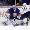 Buffalo Sabres\' Christian Ehrhoff, right, scores a goal past New York Islanders goalie Evgeni Nabokov during the second period of the NHL hockey game Saturday, Feb. 9, 2013, in Uniondale, N.Y. (AP Photo/Seth Wenig)