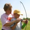 "Summer day camp director and physical therapist Jennifer Woodruff shows James ""Bo"" Cochran, of Norman, how to set up his bow and arrow during an archery session at the J. D. McCarty Center's Movin' & Groovin' summer day camp. Archery was just one of several activities the campers participated in during the week long camp. Community Photo By: Greg Gaston Submitted By: Greg,"