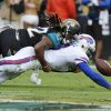 Photo - Buffalo Bills quarterback EJ Manuel, right, fumbles the ball as he is hit by Jacksonville Jaguars free safety Winston Guy, left, during the second half of an NFL football game in Jacksonville, Fla., Sunday, Dec. 15, 2013. (AP Photo/Stephen Morton)