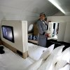 "An Etihad Airways official stands inside the 125-square-foot (11.61-square-meter) area that includes a ""living room"" partitioned off from the first-class aisle, leather seating, a chilled minibar and a 32-inch flat-screen TV, at a training facility in Abu Dhabi, United Arab Emirates, Sunday, May 4, 2014. Etihad Airways, a fast-growing Mideast carrier, laid out plans Sunday to offer passengers who find first-class seats a bit too tight a miniature suite featuring a closed-off bedroom, private bathroom and a dedicated butler. (AP Photo/Kamran Jebreili)"