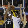 Golden State Warriors center Jermaine O\'Neal goes to the basket against San Antonio Spurs forwards Boris Diaw, left, and Aron Baynes, right, during the first quarter of their NBA basketball game Saturday, March 22, 2014, in Oakland, Calif. (AP Photo/Eric Risberg)