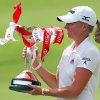 Stacy Lewis of the United States celebrates with the challenge trophy after winning the HSBC Women\'s Champions golf tournament on Sunday, March 3, 2013 in Singapore. (AP Photo/Wong Maye-E)