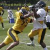 Pittsburgh Steelers linebacker Jarvis Jones (95) tries to get by running back Le\'Veon Bell (26) in a one-on-one drill at practice during NFL football training camp at the team training facility in Latrobe, Pa. on Monday, July 29, 2013. (AP Photo/Keith Srakocic)