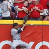 Photo - Milwaukee Brewers Carlos Gomez jumps against the wall and misses a double hit by Cincinnati Reds' Devin Mesoraco in the fourth inning of a baseball game in Cincinnati, Friday July 4, 2014. (AP Photo/Tom Uhlman)