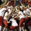 The OU Sooners surround Lauren Chamberlain (44), middle, after Chamberlain hit the game-winning home run in the twelfth inning during Game 1 of the Women\'s College World Series NCAA softball championship series between Oklahoma and Tennessee at ASA Hall of Fame Stadium in Oklahoma City, Monday, June 3, 2013. OU won 5-3 in 12 innings. Photo by Nate Billings, The Oklahoman