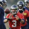 Photo - Seattle Seahawks quarterback Russell Wilson (3) has a ball tossed to him during warm-ups Wednesday, Jan. 15, 2014, before NFL football practice in Renton, Wash. The Seahawks will play the San Francisco 49ers on Sunday for the NFC championship. (AP Photo/Ted S. Warren)