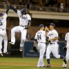 Photo - San Diego Padres' Alexi Amarista, left, and Cameron Maybin lead the celebration after the Padres' 8-2 victory over the Cincinnati Reds in a baseball game Tuesday, July 1, 2014, in San Diego. (AP Photo/Lenny Ignelzi)