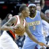 Portland Trail Blazers guard Damian Lillard, left, drives against Denver Nuggets guard Ty Lawson during the first quarter of an NBA basketball game in Portland, Ore., Thursday, Dec. 20, 2012. (AP Photo/Don Ryan)