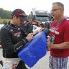 Photo - Alex Tagliani signs a gasoline container for a fan before the NASCAR Nationwide series auto race at Road America in Elkhart Lake, Wis., Saturday, June, 21, 2014.  (AP Photo/Jeffrey Phelps)