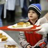 Dayton Cieszynski, 6, watches as a volunteer moves a tray carrying Dayton\'s food as the two go through the serving line. Dayton attended the event with his sister and a great aunt. Hundreds were served a traditional Christmas meal at the annual Red Andrews Dinner inside the Cox Convention Center on Christmas Day, Dec. 25, 2012. An army of volunteers showed up despite snow and ice and hazardous driving conditions. They accompanied each guest through the serving line and carried their trays and seated them at their tables. Other volunteers distributed a small mountain of toys and stuffed animals that were donated for the event. Photo by Jim Beckel, The Oklahoman