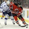 New Jersey Devils\' Ryan Carter, right, handles the puck as he is checked by Tampa Bay Lightning\'s Tom Pyatt during the first period of an NHL hockey game Tuesday, March 5, 2013, in Newark, N.J. (AP Photo/Bill Kostroun)