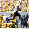 Oklahoma State\'s Tracy Moore (87) leaps over West Virginia\'s Darwin Cook (25) as he scores a touchdown during a college football game between the Oklahoma State University and West Virginia University on Mountaineer Field at Milan Puskar Stadium in Morgantown, W. Va., Saturday, Sept. 28, 2013. Photo by Sarah Phipps, The Oklahoman