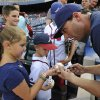 Photo - Fan favorite and former Atlanta Braves player Jeff Francoeur, right, who is now on the San Diego Padres roster, signs autographs before a baseball game between the Braves and the Padres, Friday, July 25, 2014, in Atlanta. Francoeur went to high school in the Atlanta area and was drafted by the Braves in 2002. (AP Photo/David Tulis)