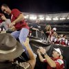 Head coach Bob Stoops helps a nephew down from the stands to join him saying