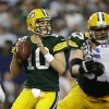 Photo - Green Bay Packers quarterback Matt Flynn (10) rolls back to pass against the Dallas Cowboys during the first half of an NFL football game, Sunday, Dec. 15, 2013, in Arlington, Texas. (AP Photo/Tim Sharp)