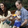 Britain\'s Kate, the Duchess of Cambridge, and her husband Prince William react as their son Prince George bites a small present that was given to him during a visit to Sydney\'s Taronga Zoo, Australia Sunday, April 20, 2014. (AP Photo/David Gray, Pool)