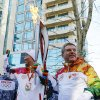 Photo - IOC President Thomas Bach, right, hands over the Olympic torch to United Nations Secretary-General Ban Ki-moon as the torch relay arrives in Sochi,  ahead of the 2014 Winter Olympics, Thursday, Feb. 6, 2014, in Russia.  (AP Photo/Shamil Zhumatov, Pool)