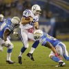 Photo - Indianapolis Colts quarterback Andrew Luck (12) is hit from both sides by San Diego Chargers inside linebacker Manti Te'o, right, and defensive end Corey Liuget during the second half of an NFL football game Monday, Oct. 14, 2013, in San Diego. (AP Photo/Lenny Ignelzi)