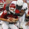 Oklahoma\'s Landry Jones (12) is sacked by Utah State\'s Nathan Royster (54) during the first half of the college football game between the University of Oklahoma Sooners (OU) and Utah State University Aggies (USU) at the Gaylord Family-Oklahoma Memorial Stadium on Saturday, Sept. 4, 2010, in Norman, Okla. Photo by Chris Landsberger, The Oklahoman