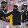 Photo - Pittsburgh Pirates starting pitcher Francisco Liriano, left, talks with pitching coach Ray Searage in the first inning of a baseball game against the Cincinnati Reds, Wednesday, April 16, 2014, in Cincinnati. Catcher Tony Sanchez listens at right. (AP Photo/Al Behrman)