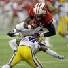 Photo - Wisconsin's Melvin Gordon leaps over LSU safety Jalen Mills (28) for a 14-yard touchdown run during the first half of an NCAA college football game Saturday, Aug. 30, 2014, in Houston. (AP Photo/David J. Phillip)