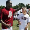 Photo - FORMER UNIVERSITY OF OKLAHOMA / OU / COLLEGE FOOTBALL PLAYER / MINNESOTA VIKINGS / NFL FOOTBALL PLAYER: Austin Tynes, 11, from Dallas, gets a pat on the head from Adrian Peterson during football camp on the University of Oklahoma campus in Norman, Okla. on Friday, June 26, 2009.  Photo by Steve Sisney, The Oklahoman ORG XMIT: KOD