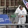 An investigator in a protective suit examines debris on Boylston Street in Boston Thursday, April 18, 2013 as investigation of the Boston Marathon bombings continues. Investigators pressed the search Thursday for one or more potential suspects spotted on video, while President Barack Obama paid a visit under heavy security to offer reassurance to the city and a warning to those responsible for the attack: