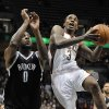 Brooklyn Nets\' Andray Blatche (0) defends as the Milwaukee Bucks\' Brandon Jennings (3) drives to the basket during the second half of an NBA basketball game Wednesday, Feb. 20, 2013, in Milwaukee. The Nets defeated the Bucks 97-94. (AP Photo/Jim Prisching)